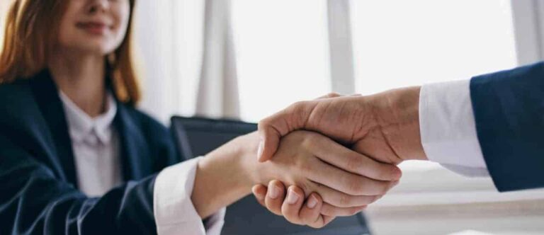 Photo of woman and man shaking hands over a settlement negotiation deal