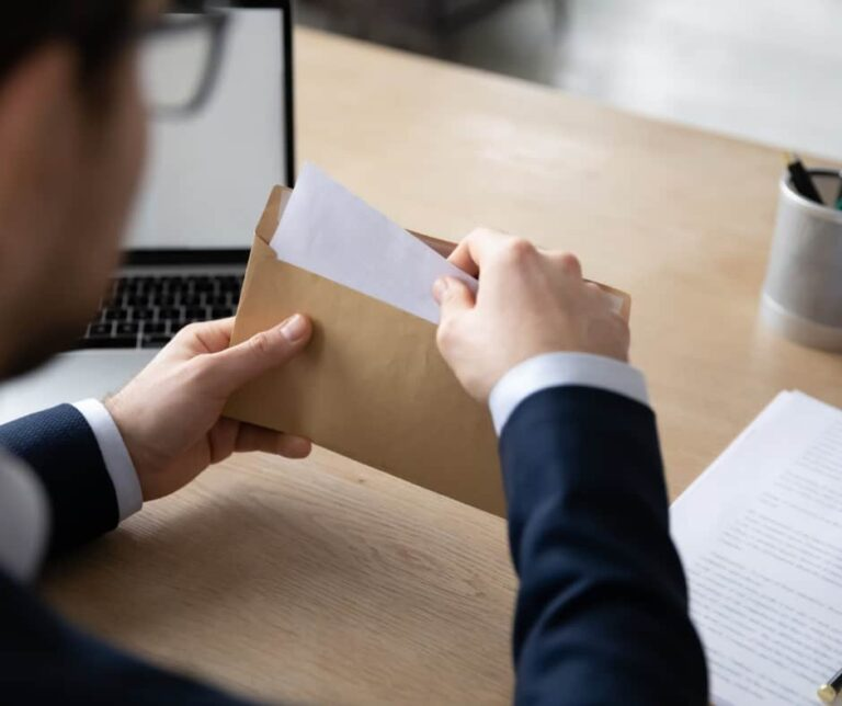 image of a man putting a check in an envelope